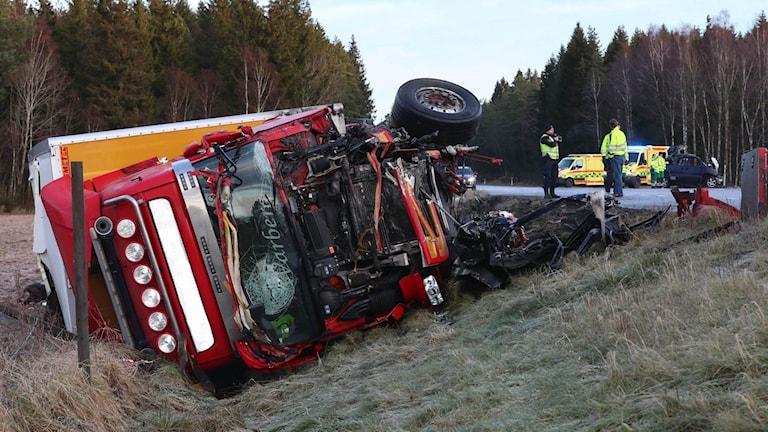 Krockskadad lastbil liggande på sidan intill vägen. Delar av personbil. Räddningspersonal.