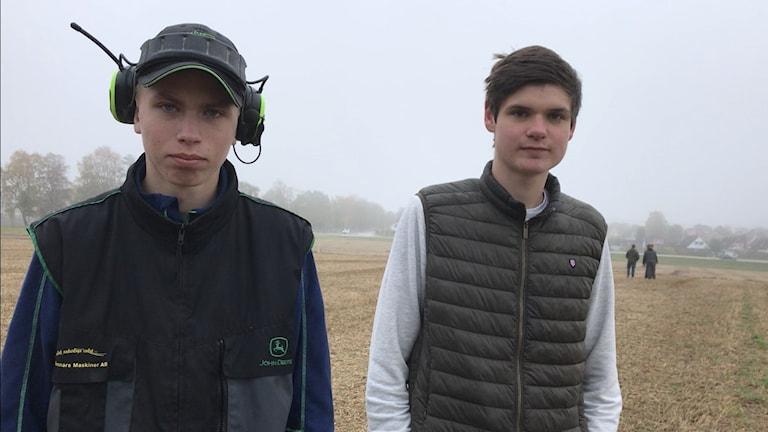 Två killar står på en åker.