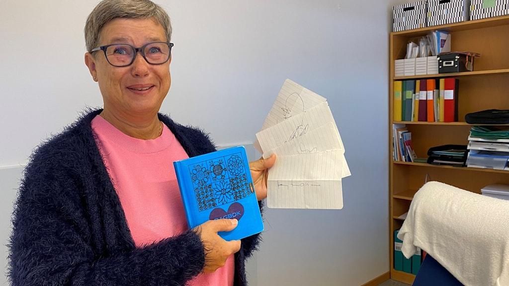 En kvinna håller upp fyra pappersark med autograferna från Abba.