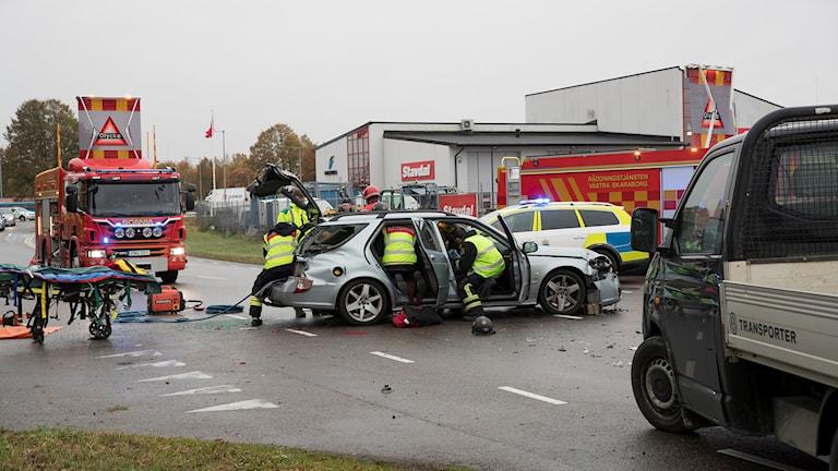 Personal från räddningstjänsten går in i personbilen som blev påkörd i en korsning. Bagageluckan var tvungen att klippas upp för att föraren skulle kunna tas ut.
