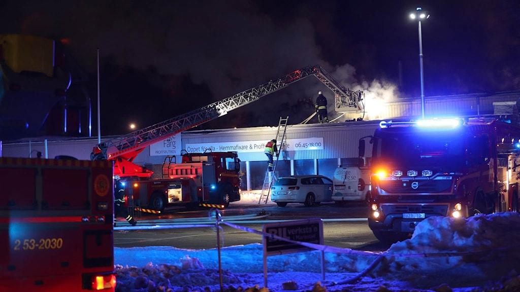 En kran med lyftkorg används för att komma åt branden från taket. Flera brandbilar. Brandman jobbar på det platta taket.