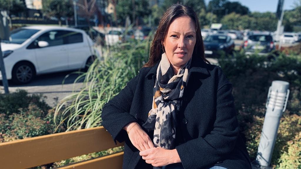 En kvinna sitter ute på en bänk.