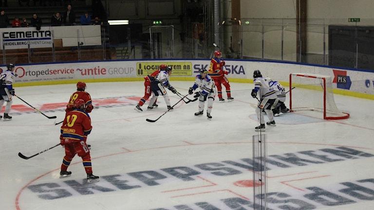 En hockeymatch pågår mellan spelare i röda och vita tröjor.
