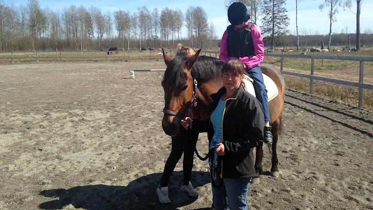 Barn sitter upp på häst medan en vuxen håller i tyglarna.