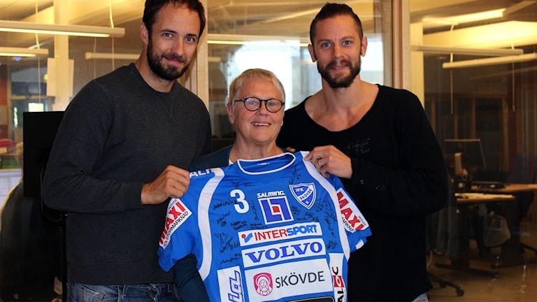 Kristian Svensson Margareta Lilja och Rasmus Wremer framför den handbollströja som budas ut till förmån för världens barn.