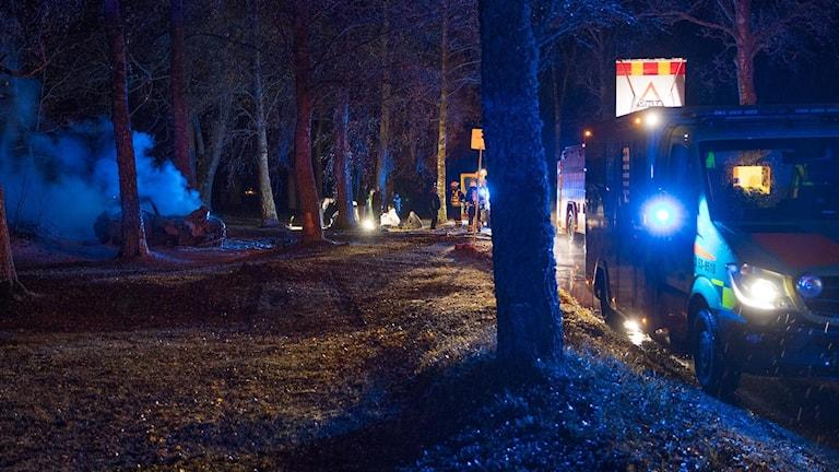 Bil som släckts efter brand, personer som sitter på marken med en filt om sig, räddningspersonal och räddningsfordon.