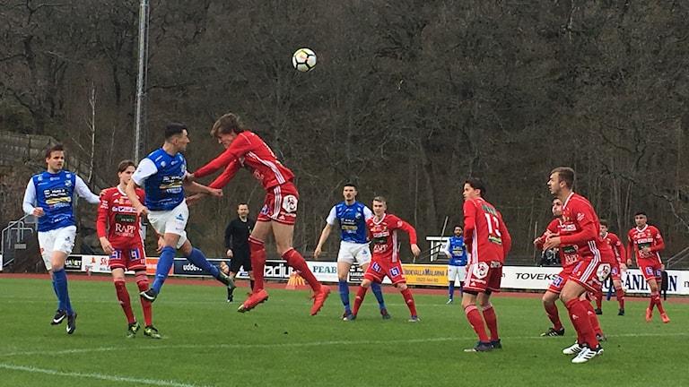 Ett fotbollslag i röda tröjor möter ett lag i blå tröjor.