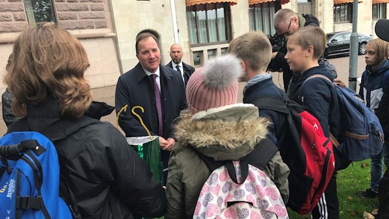 Statminister Stefan Löfven står ute och pratar med en grupp barn.