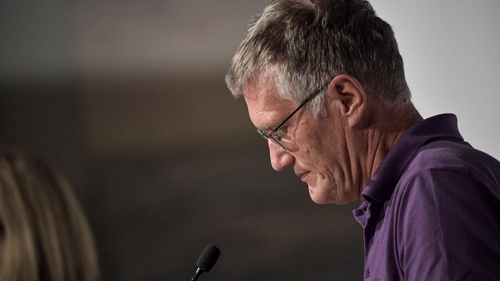 En man i glasögon och lila pikétröja tittar ned med böjt huvud.