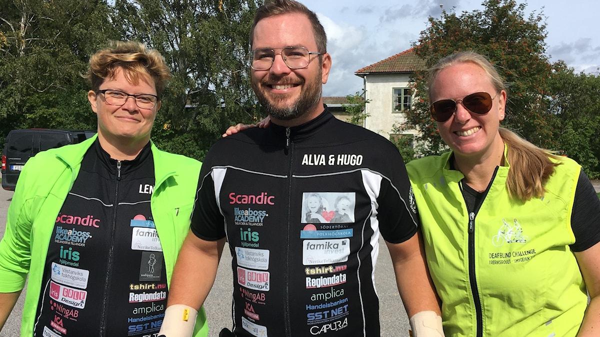 Tre glada personer i solskenet med cykelkläder.
