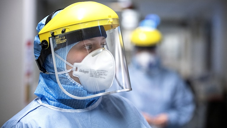 En kvinna med munskydd och visir.