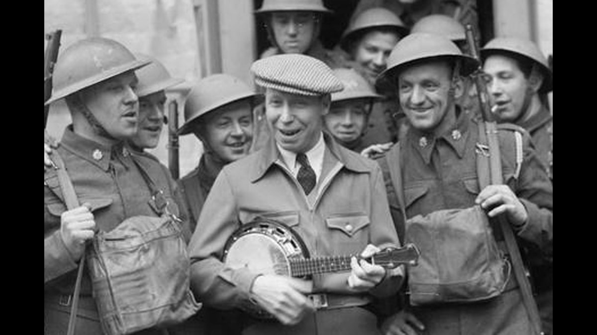 George Formby underhåller brittiska trupper 1940. Foto: War Office official photographer Puttnam L A (Lt) [Public domain], via Wikimedia Common.