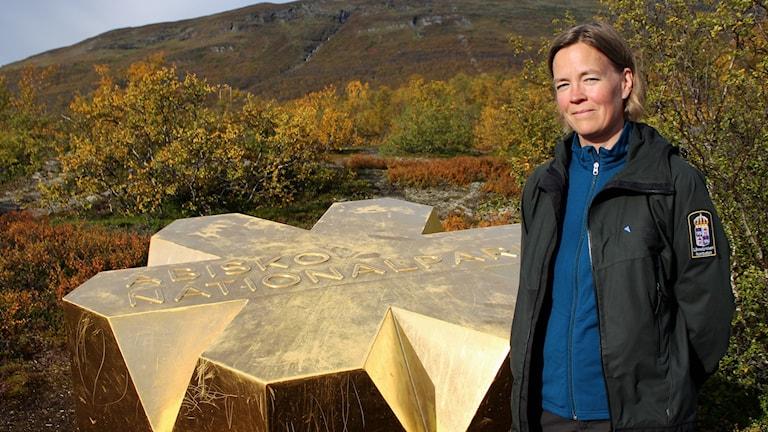 En cirka 800 kilo tung nationalparkssymbol har placerats i Abisko. Projektledaren Anna Berhan från länsstyrelsen står bredvid guldkronan.
