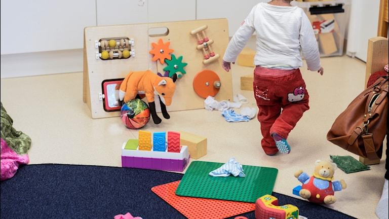 Bild på ett barn i ett lekrum på förskola.