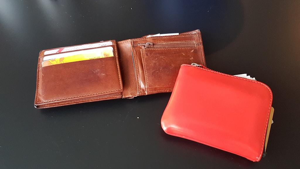 En röd och en brun plånbok på ett svart bord.