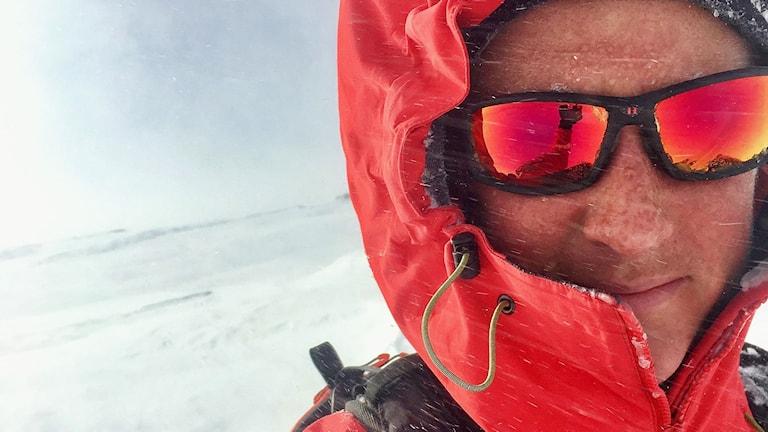Jenny Råghall, lavintekniker i Abisko och Riksgränsen, utomhus i röd räddningsjacka och solglasögon.
