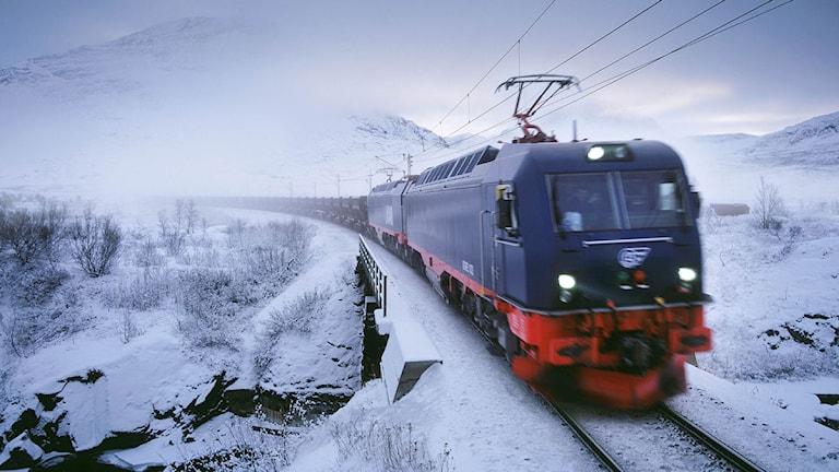 Ett malmtåg som färdas genom snöiga fjäll