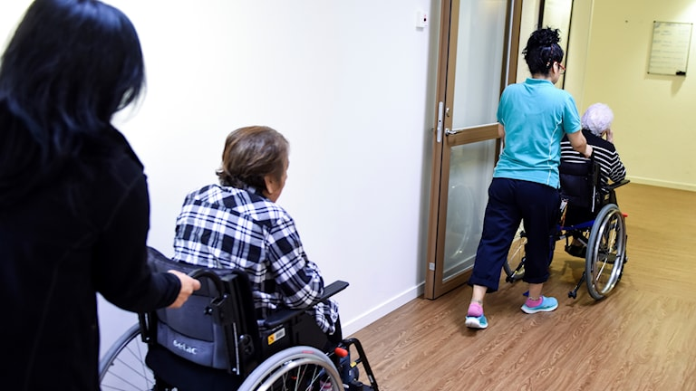 Anställda på äldreboende rullar två personer i rullstol.