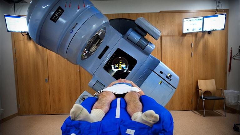 Person ligger på sjukhusbädd under en strålningskanon.
