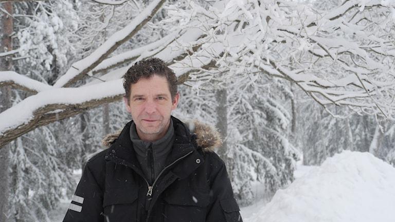 David Chapman står bland snöbetäckta träd.