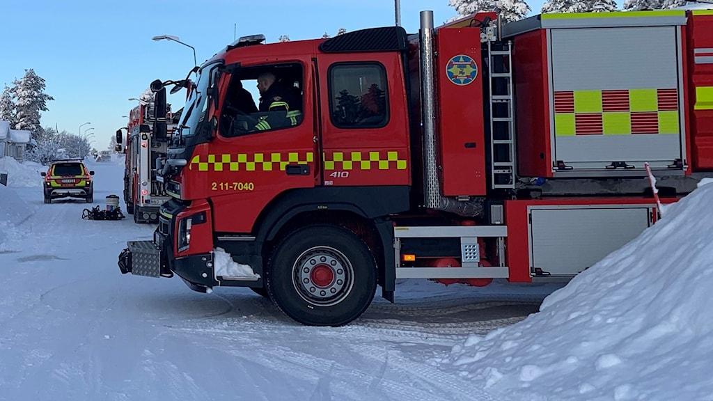 Brandbilar i snötäckt villaområde.