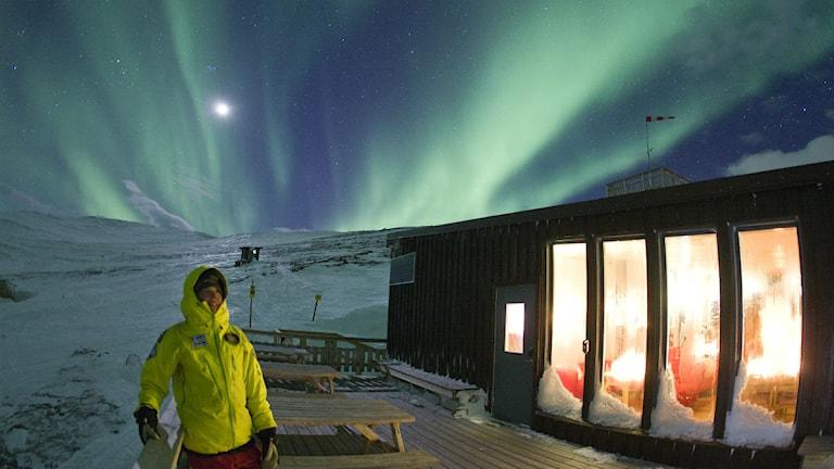 En turist står vid STF Aurora Sky Station i Abisko med Norrsken i Bakgrunden. Foto: Peter Rosén