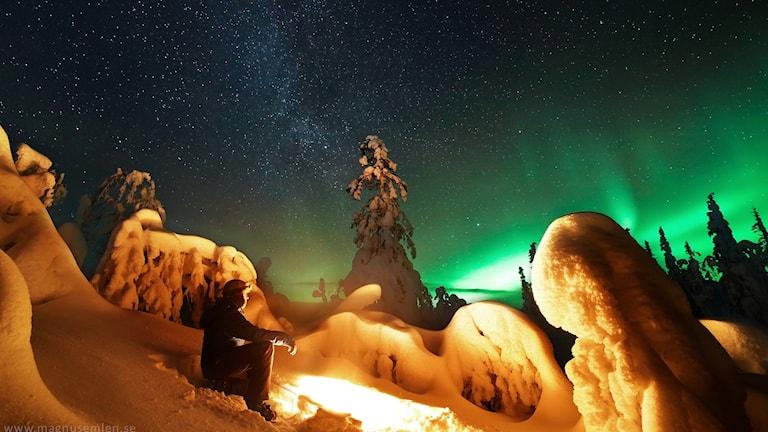Magnus Emlén lyses upp av norrsken, vintergatan och brasan i ett vintervitt snölandskap.
