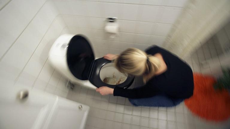 En tjej som kräks på toaletten.