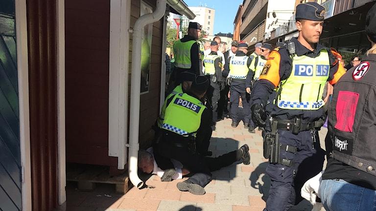 Här brottas kommunalrådskandidaten Bo Nilsson (NMR) ner av polis.