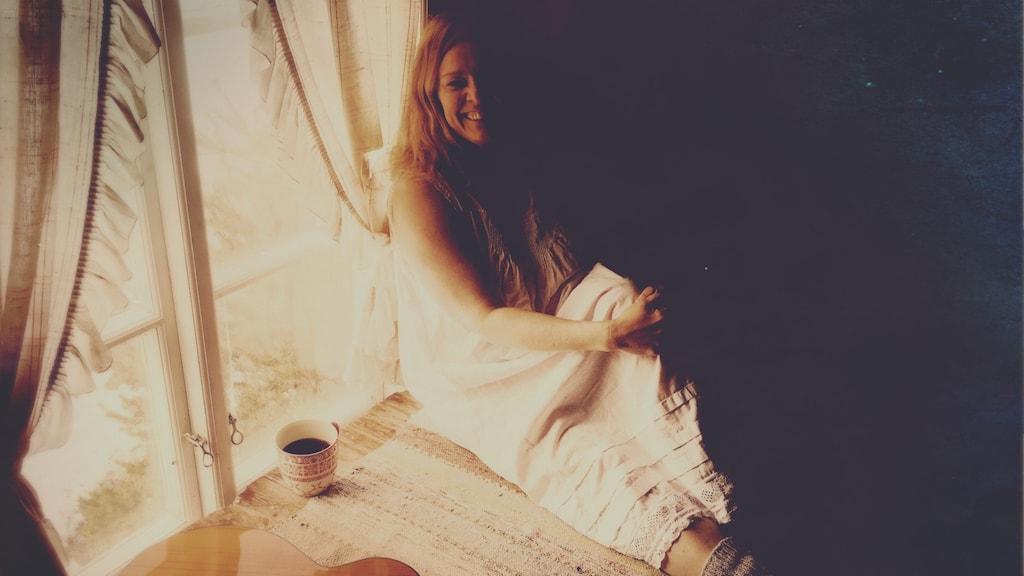 Anna Sellén sitter vi ett fönster med en kaffekopp bredvid sig.