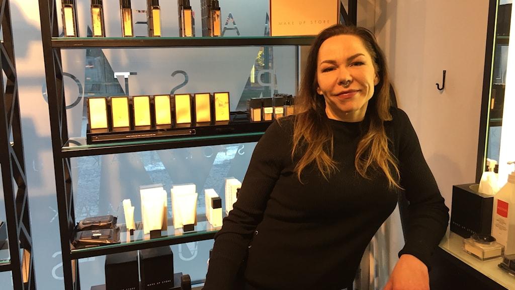 En bild på ia Brönnholm framför sminkprodukter.