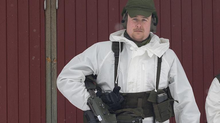 Soldat i vit vinterdräkt står mot en vägg