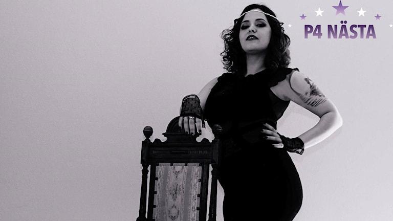 Artisten Prana Belle står och lutar kaxigt på en stolsrygg.