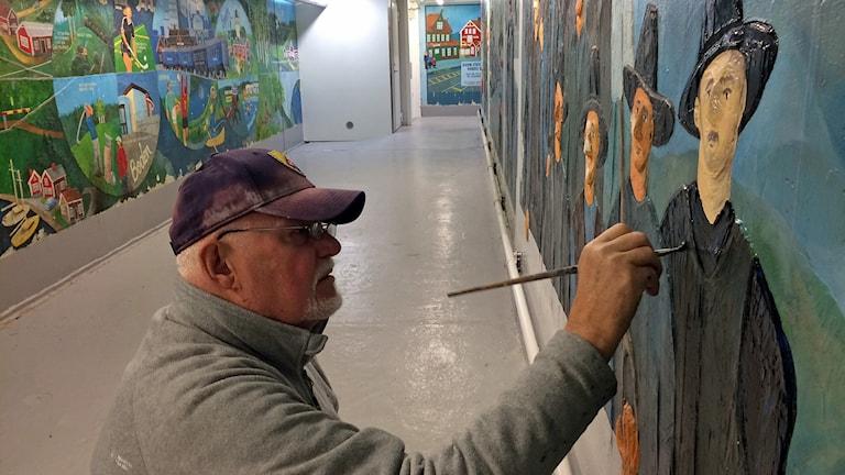 Anders Hjortenklev, konstnär i Boden, retuscherar 25 år gamla målningar i tunneln vid järnvägsstationen.