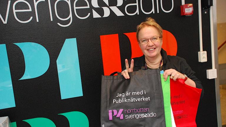 Publikredaktör Eva Elke visar upp påsarna som delas ut till medlemmarna i P4 Norrbottens publiknätverk. Foto: Sveriges Radio.
