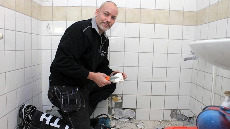 Doktorand Dan Jönsson från Lunds tekniska högskola undersöker ett våtrum i en lägenhet som ska rivas till följd av Kirunas stadsomvandling. Foto: Alexander Linder/ Sveriges Radio.