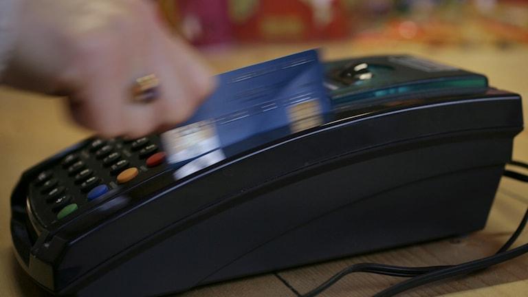 Ett bankkort dras i en kortterminal. Foto Fredrik Sandberg/TT