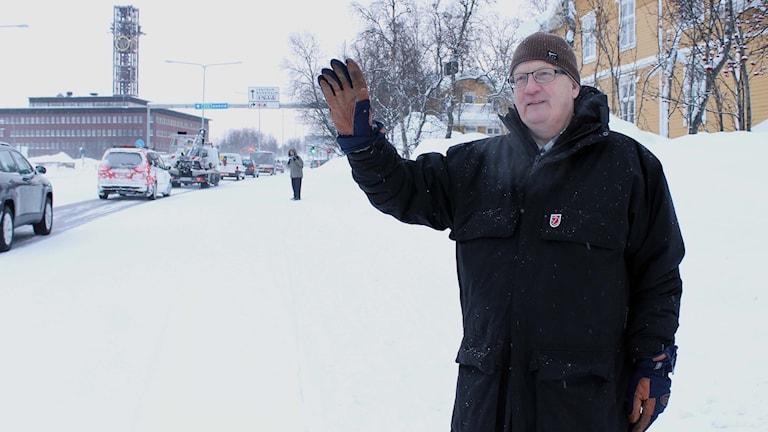 Håkan Sandström gillar inte att E10:ans trafik ska ledas genom centrala Kiruna. Här vinkar han till en förbipasserande bilist. Foto: Alexander Linder/ Sveriges Radio.