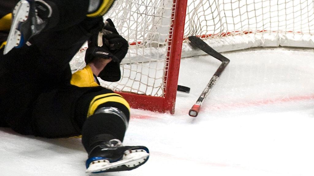 Ishockeyklubba, puck och liggande ishockeyspelare på isen. Foto: Claudio Bresciani/TT.