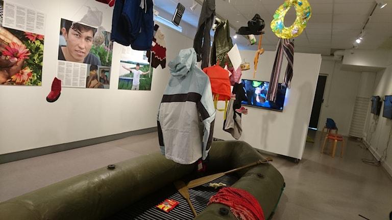 En gummibåt på Norrbottens museum. Över den hänger kläder och andra personliga tillhörigheter.