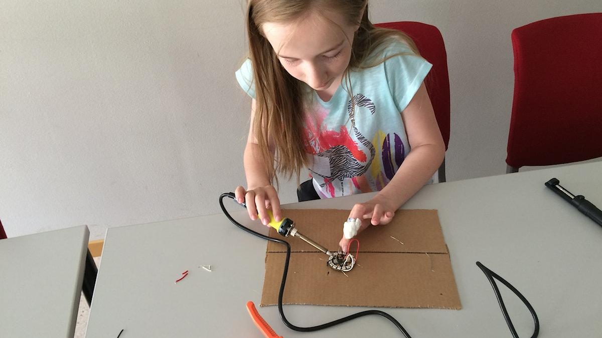 Anja Omark, 11 år i, löder ett lysande smycke. Foto: Marcus Nilsson/Sveriges Radio