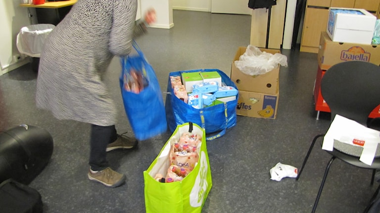 Flera påsar med mat och leksaker till flyktingarna. Några av de som samlat in mat, leksaker och kläder till flyktingarna som kom till Luleå idag. Foto: Marcus Nilsson/Sveriges Radio.