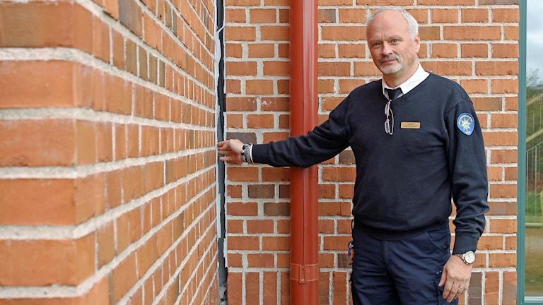 Insatschef Hans Stenmark i Kiruna räddningstjänst visar en stor glipa i brandstationen. Foto: Alexander Linder/ Sveriges Radio.