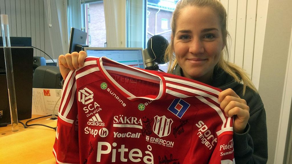 Piteå IF:s Irma Helin med den signerade matchtröjan som auktioneras ut för Världens barn. Foto: Lena Callne/Sveriges Radio.