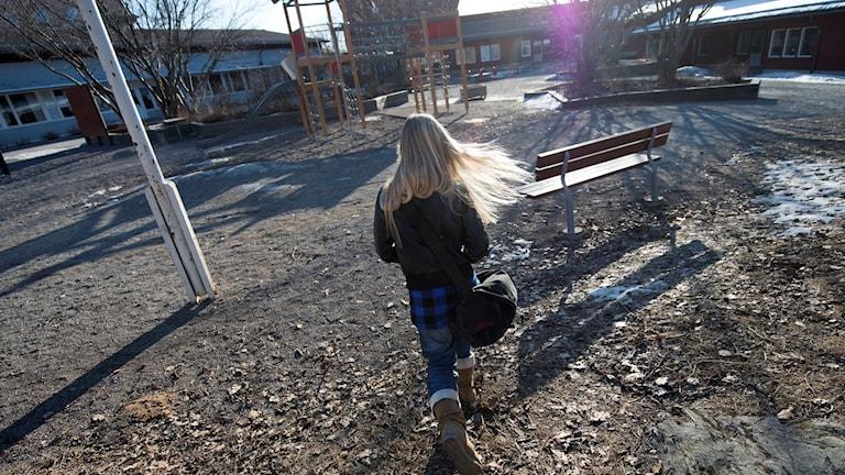 Ensam flicka går över en skolgård med skolväskan på axeln. Foto: Fredrik Sandberg/TT.
