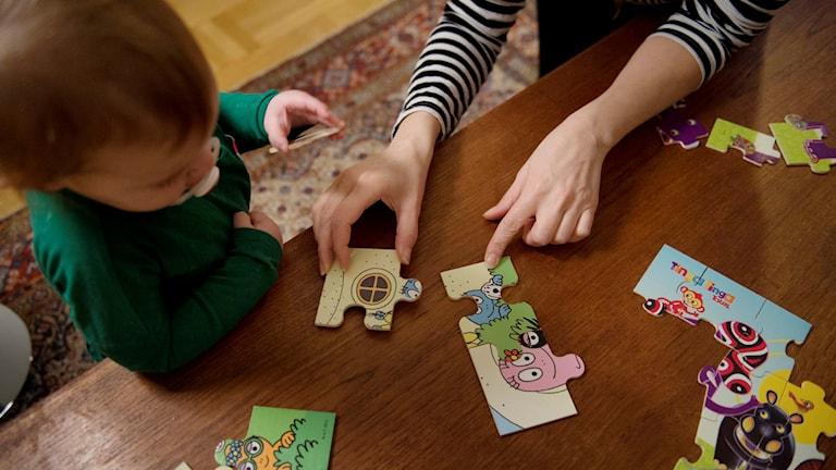 Förälder lägger pussel med litet barn. Foto: Jessica Gow/TT.