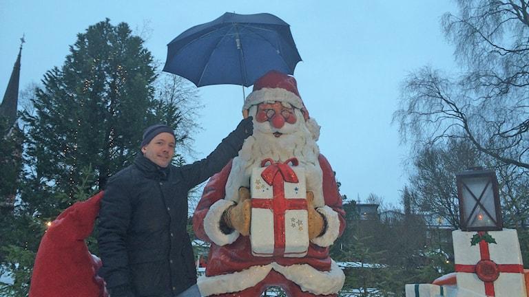 Meteorologen Andreas Livbom håller ett paraply över Tomtens huvud. Foto: Anneli Lindbäck/Sveriges Radio