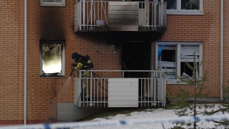 Brandman på balkongen till den eldhärjade lägenheten på Björkskatan i Luleå. Foto: Patrik Boström/Sveriges Radio