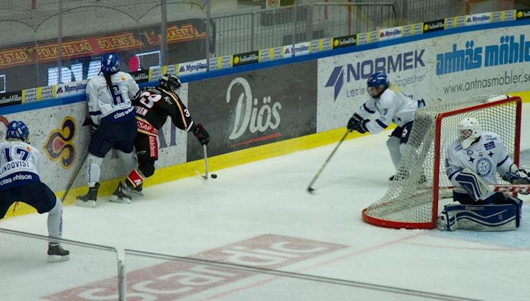 Hockeyrink vitklädda och mörka hockeyspelare.