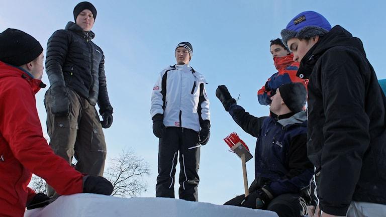Ett av lagen i snöskulpturtävlingen består av elever från Hjalmar Lundbohmsskolan i Kiruna. Foto: Alexander Linder/ Sveriges Radio.